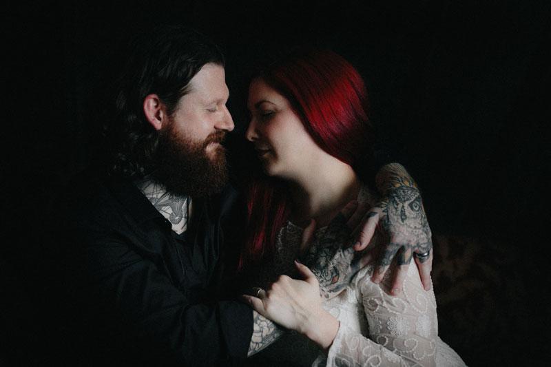 dark portrait tattooed couple engage